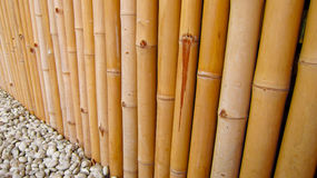 Bamboo fence with stones perspective Royalty Free Stock Photo
