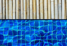 A bamboo floor next to a pool Stock Images
