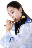 Bamboo flute performer. Chinese musician in traditional dress playing the flute on white.(close-up Royalty Free Stock Images