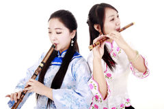 Bamboo flute performer. Two Chinese musicians in traditional dress playing bamboo flute on white Stock Image