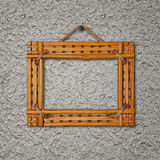 Bamboo frame on gray stucco concrete wall. Stock Image