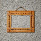 Bamboo frame on gray stucco concrete wall. Stock Image