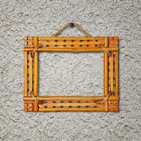 Bamboo frame on gray stucco concrete wall. Royalty Free Stock Image