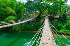 Bamboo hanging bridge over river Stock Photos