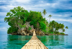 Bamboo hanging bridge over sea to tropical island. Bamboo pedestrian hanging bridge over sea to remote desert island. Beautiful tropical landscape. Travel Royalty Free Stock Photo