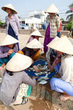 Bamboo hat Vietnamese women choose fish to sell in market Royalty Free Stock Photo