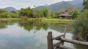 Bamboo hut offers serenity in Thailand. A bamboo hut reflects on the water with mountains in the background stock photography