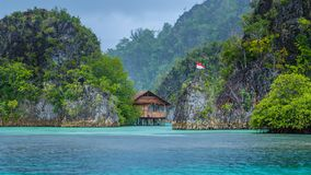 Bamboo Hut between some Rocks under Rain in Bay with Indonesian Flag, Pianemo Islands, Raja Ampat, West Papua, Indonesia.  royalty free stock photo