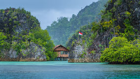 Bamboo Hut between some Rocks under Rain in Bay, Painemo Islands, Raja Ampat, West Papua, Indonesia. Bamboo Hut between some Rocks under Rain in Bay, Painemo royalty free stock photography