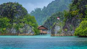 Bamboo Hut between some Rocks under Rain in Bay, Painemo Islands, Raja Ampat, West Papua, Indonesia. Bamboo Hut between some Rocks under Rain in Bay, Painemo Royalty Free Stock Image