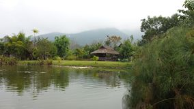 Bamboo hut on the water in Thailand. A bamboo hut provides solace and peaceful refuge along the water in northern Thailand in Pai. A reflection on the water and stock photos