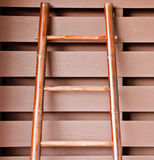 Bamboo ladder laying on wooden wall Stock Images