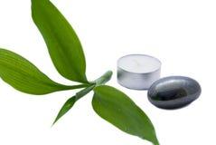 Bamboo leaf with massage stone. Isolated on white Royalty Free Stock Photos