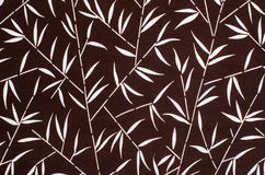 Bamboo leaves pattern on brown fabric. royalty free stock image