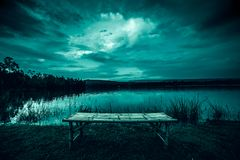 Bamboo litter on grass in front of lake and moonlight behind a cloudy at night time. Empty of bamboo litter on grass. moonlight shines behind a cloudy at night royalty free stock photography
