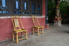 Bamboo-made chairs before latticed window of aged building Royalty Free Stock Image