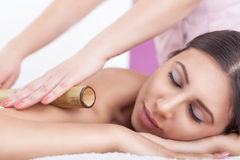 Bamboo massage. Young Woman Enjoy Bamboo massage at spa centre Stock Image