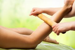 Bamboo massage on female leg. royalty free stock photography