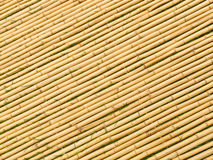 Bamboo Mat Angled Sticks. Bamboo tied together to form a mat with blades of grass between each angled stick Royalty Free Stock Image