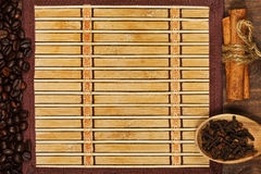 Bamboo mat with frame of coffee beans and condiments. Bamboo square mat with wooden spoon with clove seed, cinnamon sticks and roasted coffee beans in top view stock photo