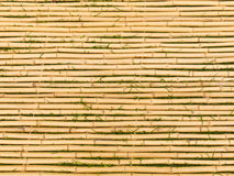 Bamboo Mat with Horizontal Sticks. Bamboo tied together to form a mat with blades of grass between each horizontal stick Stock Image