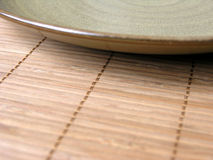 Bamboo Mat and Plate 3. A stoneware plate on a bamboo place mat with shallow depth of field Stock Images