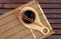 Bamboo mat, soy sauce, chopsticks on dark wooden table. Top view with copy space royalty free stock photos