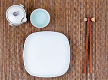 Bamboo mat with traditional Asian utensils plus white dinner pla Stock Image