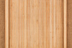 Bamboo mat twisted in the form of a manuscript on sackcloth Royalty Free Stock Images