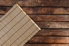 Bamboo mat on wooden table Royalty Free Stock Photo
