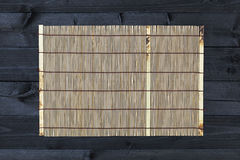 Bamboo mat on wooden table, top view stock photography