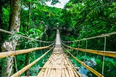 Bamboo pedestrian suspension bridge over river Stock Images