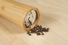 bamboo pepper grinder with grains on the table Stock Image