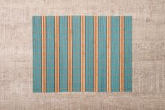 Bamboo place mat. On wooden deck table Royalty Free Stock Photo
