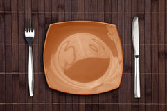 Bamboo placemat with square plate fork and knife Royalty Free Stock Photos