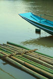 Bamboo raft and blue boat on water Stock Photography