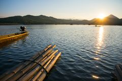 Bamboo  raft and boat in reservoir sunset. Beautiful sunset in reservoir with fisherman on wooden boat.tourist on bamboo raft Stock Photography