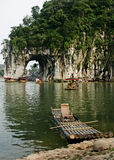A bamboo raft in front of Elephant Trunk Hill. An empty bamboo raft with a bamboo chair anchored to the shore with the Elephant Trunk Hill as background Royalty Free Stock Images