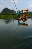 Man Rowing bamboo raft. Reflection Man rowing bamboo raft Yulong Li River China Stock Image