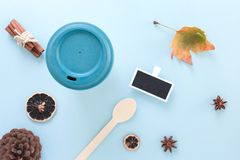 Bamboo reusable takeaway cup with lid on with autumn leaf, wooden spoon and other objects, flat lay on blue background.  stock photos