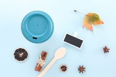 Bamboo reusable takeaway cup with lid on with autumn leaf, wooden spoon and other objects, flat lay on blue background.  stock photography