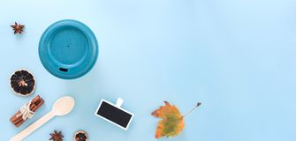Bamboo reusable takeaway cup with lid on with autumn leaf, wooden spoon and other objects, flat lay on blue background.  royalty free stock image