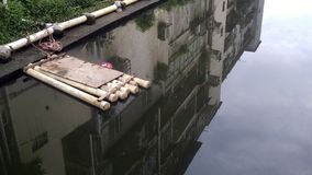 A bamboo row in the river and the surrounding buildings reflected in the water. A bamboo row in the river and the surrounding buildings reflected in the water Stock Photography