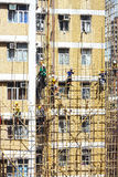 Bamboo scaffold constructions. A group of Chinese workers busy constructing temporary bamboo scaffold around a building which need of repairing Stock Photography