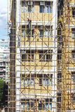 Bamboo scaffold constructions. A group of Chinese workers busy constructing temporary bamboo scaffold around a building which need of repairing Stock Photos