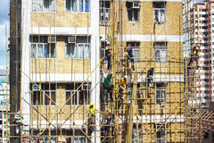 Bamboo scaffold constructions. A group of Chinese workers busy constructing temporary bamboo scaffold around a building which need of repairing Stock Photo