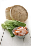 Bamboo steamer, bok choy and prawns stock images