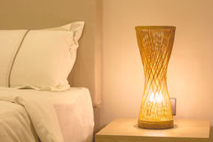 Bamboo table lamp orange near bad Stock Images