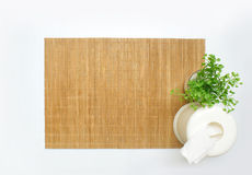 Bamboo table mat with a small plant and a tissue box. On white background Stock Photo