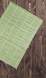 Bamboo tablecloth on wooden table over grunge background. Stock Photos